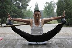 <p>A man stretches himself during a morning exercise session at a park in Beijing June 18, 2009. REUTERS/Grace Liang</p>