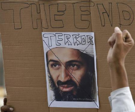 A member of the All India Anti-Terrorist Front (AIATF) gestures in front of a portrait of al-Qaeda leader Osama bin Laden during a pro-U.S. rally as the group celebrates bin Laden's killing, in Noida May 5, 2011. REUTERS/Parivartan Sharma