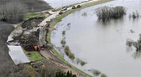 <p>Work continues along Provincial Highway 331 as preparations are made to break the dike south east of Portage la Prairie, Manitoba May 11, 2011. REUTERS/Fred Greenslade</p>