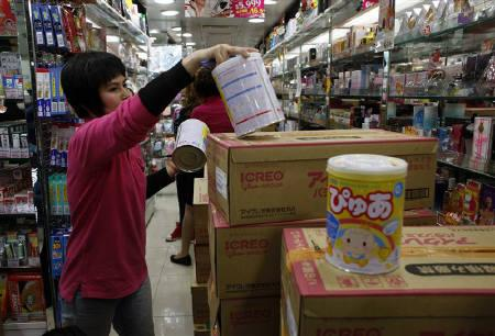 A staff member unpacks Japanese milk powder for a customer inside a store in Hong Kong March 16, 2011. The world's leading baby milk companies still flout a global code on marketing breast milk substitute, a campaign group said on Thursday, the eve of the 30th anniversary of its adoption. REUTERS/Bobby Yip/Files
