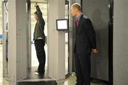 Transportation Security Administration employees demonstrate new body scanner software that uses a stick figure to represent the passenger being scanned, rather than an actual image of the person, at the TSA Systems Integration Facility at washington's Reagan National Airport in Arlington, Virginia, February 1, 2011. REUTERS/Jonathan Ernst