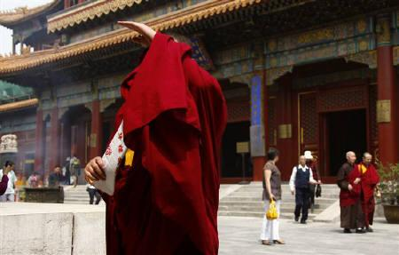 A Buddhist monk covers his face from a photographer at the Yonghegong Lama Temple in Beijing May 23, 2011. REUTERS/David Gray