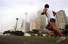 <p>A jogger runs towards a fog shrouded Sydney city skyline May 15, 2008. REUTERS/Tim Wimborne</p>