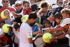 Thomaz Bellucci dá autográfos a fãs após vencer o italiano Andreas Seppi em Roland Garros. 25/05/2011  REUTERS/Charles Platiau