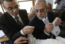 <p>Muslim Brotherhood leader Mohammed Badie (R) casts his vote during a national referendum at a school in Cairo March 19, 2011. Egyptians flocked to the polls on Saturday in a histo REUTERS/Amr Abdallah Dalsh</p>