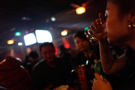 A woman drinks at a bar in a nightclub in Shanghai February 25, 2010. REUTERS/Aly Song