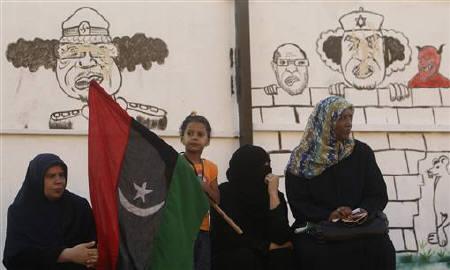 Libyan women sit near drawings of Libyan leader Muammar Gaddafi near a courthouse in Benghazi May 31, 2011. REUTERS/Mohammed Salem