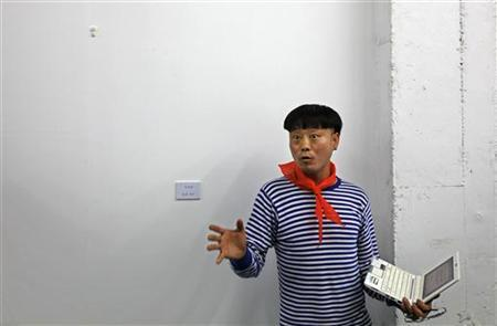Fei Xiaosheng, an organizer of the Third Incidental Art Festival gestures in front of the wall left blank in support of detained artist-activist Ai Weiwei, during the opening ceremony in Beijing June 1, 2011. REUTERS/Petar Kujundzic