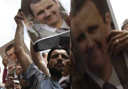 Protesters chant slogans in support of Syrian President Bashar al-Assad as they carry his pictures outside al-Omari mosque, where another demonstration to express solidarity with Syria's anti-government protesters is taking place, in downtown Beirut June 3, 2011. REUTERS/ Mohamed Azakir