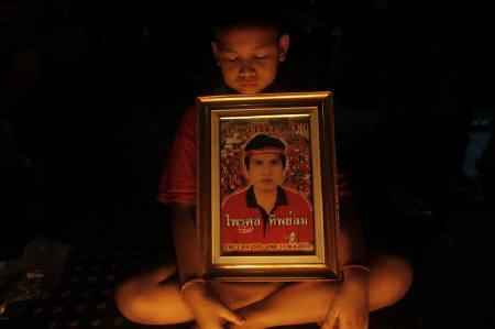 A boy holds a photo of his father who was killed in violent protests last year during anti-government ''red shirt'' rally at Ratchaprasong intersection at Bangkok's shopping district May 19, 2011. REUTERS/Damir Sagolj/Files