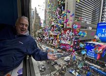 <p>John Heald, senior cruise director for Carnival Cruise Lines, tosses confetti from a window overlooking Times Square in New York December 29, 2010 to test air currents in preparation for the upcoming New Year's Eve celebration. REUTERS/Ray Stubblebine/Carnival Cruise Lines/Handout</p>