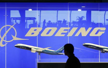 A man looks at a scale model of a Boeing aircraft at their booth at the Singapore Air Show in this February 19, 2008 file photo. Gulf carrier Qatar Airways placed an order for six Boeing 777-300ER wide-body jets worth $1.7 billion at list prices. REUTERS/Vivek Prakash/Files
