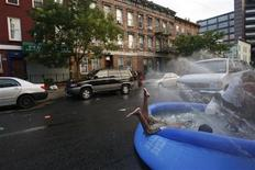 <p>Children cool off in a inflatable pool in an effort to beat the heatwave in the Brooklyn section of New York July 6, 2010. REUTERS/Jessica Rinaldi</p>