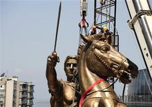 <p>Workers lift a massive statue of Alexander the Great on his horse Bucephalus in Skopje central square June 21, 2011. REUTERS/Ognen Teofilovski</p>