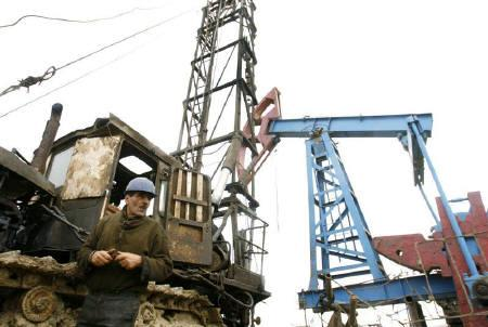 A workers stands beside an oil pump jack in Baku March 17, 2009.  REUTERS/David Mdzinarishvili/Files