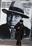 <p>A woman walks past grafitti of Al Capone in downtown Belgrade, March 17, 2010. REUTERS/Marko Djurica</p>