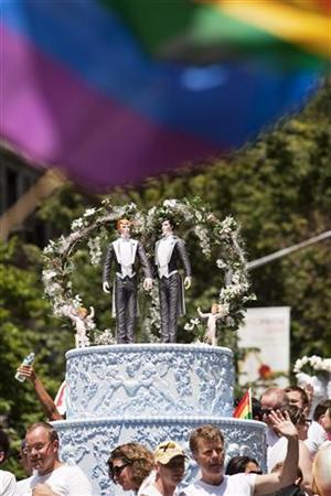 Two grooms are placed atop a wedding cake to protest in favor of gay marriage in the annual Gay Pride Parade in New York June 28, 2009. REUTERS/Jacob Silberberg