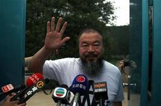 O artista dissidente chinês Ai Weiwei acena a jornalistas na porta de seu estúdio depois de ser libertado sob fiança, em 23 de junho, em Pequim, na China. 23/06/2011  REUTERS/David Gray