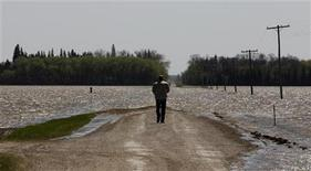 <p>A man looks at a flooded farm field from a deliberate breach of a dike on the Assiniboine River near Newton, Manitoba May 17, 2011. REUTERS/Shaun Best</p>