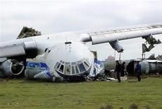 Люди стоят рядом с упавшим под Баку самолетом Ил-76, 4 марта 2004 года. Грузовой самолет Ил-76 азербайджанской частной авиакомпании с девятью членами экипажа упал в двух десятках километров к северу от Кабула в ночь на среду, сообщили местные власти и администрация гражданской авиации Азербайджана. REUTERS/Str