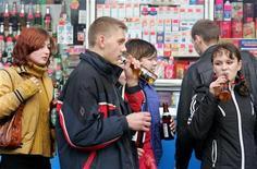 Молодые люди пьют пиво около киоска в Москве 28 октября 2004 года. РФ предлагает полностью запретить продажу всех видов пива ночью и в киосках с января 2013 года, приравняв пенный напиток к алкогольной продукции.  REUTERS/Sergei Karpukhin