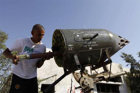 A Libyan rebel fighter loads his vehicle-mounted rocket launcher at a checkpoint in Bir Ayyad July 1, 2011. REUTERS/Anis Mili/Files