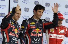 O australiano Mark Webber (centro), da Red Bull, posa para foto com os colegas Sebastian Vettel (esquerda), da Alemanha, e Fernando Alonso (direita), da Espanha, após se qualificar para o Grande Prêmio da Inglaterra, em Silverstone, Grã-Bretanha. 09/07/2011 REUTERS/Nigel Roddis