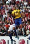 O zagueiro Lúcio disputa lance com o paraguaio Cristian Riveros em jogo da Copa América no dia 9 de julho. O brasileiro pediu à seleção mais comprometimento em campo após dois empates na competição.   REUTERS/Enrique Marcarian