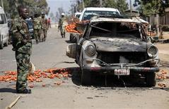 <p>A soldier stands near a burned vehicle which was carrying tomatoes along a road in Nigeria's central city of Jos, January 20, 2010. REUTERS/Akintunde Akinleye</p>