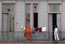<p>A woman looks out from her balcony in Havana July 11, 2011. REUTERS/Enrique De La Osa</p>