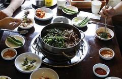 Люди едят собачье мясо в ресторане в Сеуле 14 июля 2011 года. Четверг стал не самым лучшим днем для южнокорейских собак: согласно корейскому лунному календарю, в этот день столбики термометра поднимаются до самых высоких значений, а суп из мяса собаки помогает лучше перенести жаркую погоду.   REUTERS/Truth Leem