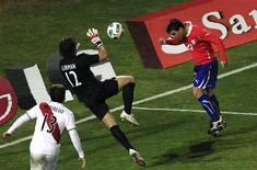 Atacante chileno Paredes cabeceia contra o goleiro peruano Libman em partida da Copa América. 12/07/2011 REUTERS/Ivan Alvarado