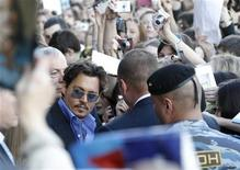 """<p>Actor Johnny Depp is surrounded by fans and security after arriving for the premiere of his new film """"Pirates of the Caribbean:On Stranger Tides"""" at the Oktyabr Cinema in Moscow May 11, 2011. REUTERS/Sergei Karpukhin</p>"""