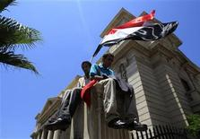 Protesters carry flags and sit on a wall at Al Qaed Ibrahim Mosque while taking part in Friday prayers in the Mediterranean city of Alexandria, 230 km (140 miles) north of Cairo July 15, 2011. REUTERS/Amr Abdallah Dalsh