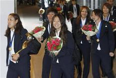 """Jogadoras da seleção japonesa de futebol, Nozomi Yamago (esq), segurando o troféu, Homare Sawa (esq) e outras jogadoras seguram buquês de """"Nadeshiko"""", ao chegar no aeroporto de Narita, em Tóquio. O Japão deu à sua seleção feminina de futebol um tratamento de estrelas de rock em seu retorno ao país após uma deslumbrante conquista do título na Copa do Mundo da Alemanha. 19/07/2011     REUTERS/Kyodo"""