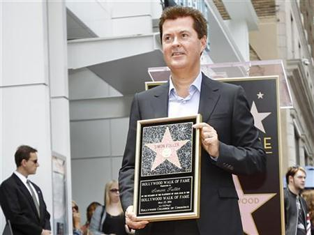 Producer Simon Fuller poses on his star on the Walk of Fame in Hollywood, California May 23, 2011. REUTERS/Mario Anzuoni