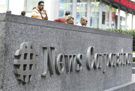 Pedestrians walk past a sign outside of the News Corporation Headquarters building in New York July 22, 2011. REUTERS/Lucas Jackson