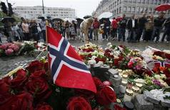 A Norwegian flag sticks out of a bunch of red roses as a woman places flowers on the market square outside the Oslo cathedral as hundreds mourn the victims of a bomb blast in the Norwegian capital and a rampage on an island in the countryside July 23, 2011. REUTERS/Wolfgang Rattay