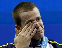 O nadador Cesar Cielo chora no pódio depois de conquistar o título mundial dos 50 metros borboleta, em Xangai, na China. 25/07/2011 REUTERS/David Gray