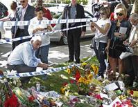 Mitch e Janis Winehouse, pais da cantora britânica Amy Winehouse, olham os presentes deixados por fãs do lado de fora da casa dela em Londres. 25/07/2011  REUTERS/Luke MacGregor