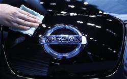 Женщина протирает автомобиль Nissan Motor на автошоу в Иокогаме, 27 июня 2011 года. Операционная прибыль Nissan Motor Co снизилась на 10 процентов в апреле-июне 2011 года из-за возникновения дефицита ряда комплектующих после землетрясения в Японии 11 марта. REUTERS/Yuriko Nakao