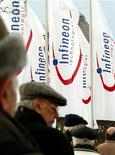 Люди стоят около флагов с логотипом Infineon Technologies в Мюнхене, 21 января 2003 года. Прибыль и продажи немецкого производителя чипов Infineon Technologies AG оказались выше средних ожиданий аналитиков, благодаря высокому спросу со стороны автопроизводителей и других промышленных клиентов. REUTERS/Alexandra Winkler