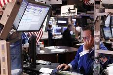 Трейдер Уолл-стрит следит за торгами в Нью-Йорке, 25 июля 2011 года. Акции на Уолл-стрит подешевели во второй половине торгов четверга и закончили день на отрицательной территории, так как инвесторы не слишком поверили, что голосование в Конгрессе поможет выйти переговорам о долговом лимите из тупика и избежать дефолта.  REUTERS/Lucas Jackson
