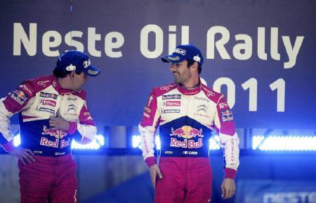 French driver Sebastien Loeb (R) and his co-driver Daniel Elena celebrate their victory of the FIA World Rally Championship WRC Neste Oil Rally on the podium in Jyvaskyla, Finland July 30, 2011. REUTERS/Martti Kainulainen/Lehtikuva