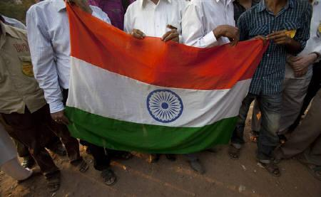 Demonstrators stand with an Indian national flag during a protest rally against corruption in Mumbai April 8, 2011. REUTERS/Vivek Prakash/Files