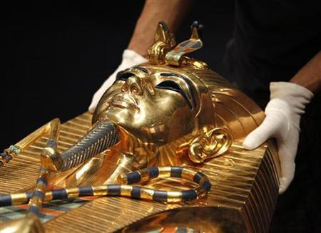 A worker arranges a replica of a sarcophage of Pharaoh Tutankhamun ahead of the opening of a major exhibition on the Ancient Egypt called 'Tutankhamun, his Tomb and his Treasures' in Brussels April 11, 2011. REUTERS/Yves Herman