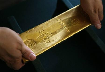 A man holds a gold bar at the national bank headquarters in Warsaw June 17, 2011. REUTERS/Kacper Pempel/Files