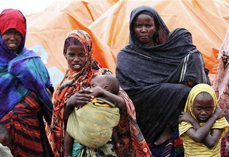 An internally displaced Somali family stand the rain outside their makeshift shelter in the south of Mogadishu's Hodan district August 2, 2011. REUTERS/Omar Faruk