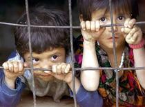 Таджикские дети выглядывают из бесстекольной оконной рамы в деревне, находящейся в 35 километрах от Душанбе, 23 октября 2001 года. Таджикистан запретил подросткам молиться в мечетях и церквях, ходить в ночные клубы, смотреть боевики и носить украшения, объяснив расстроившие верующих, правозащитников и Запад нововведения заботой о светском укладе жизни и предотвращении экстремизма. REUTERS/Alexander Demianchuk