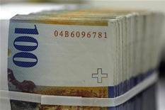 Стопка банкнот по 100 швейцарских франков в банке в Лозанне, 17 февраля 2011 года. Швейцарский франк резко снизился к доллару и евро в ходе торгов четверга в ожидании интервенции со стороны центробанка, однако трейдеры пока не видят признаков выхода ЦБ Швейцарии на валютный рынок. REUTERS/Denis Balibouse